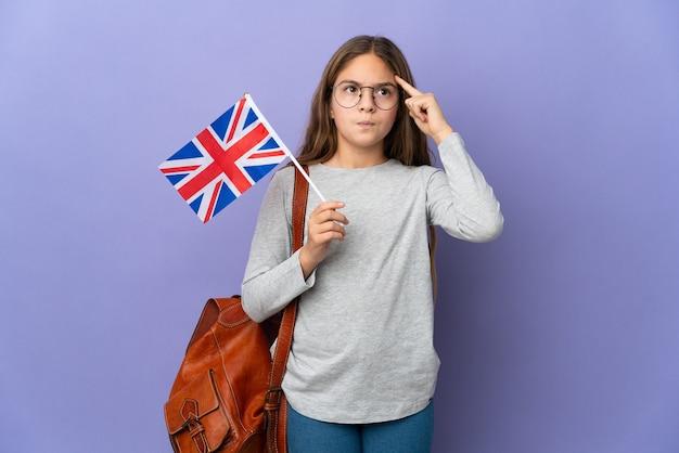Ребенок держит флаг соединенного королевства на изолированном фоне, сомневаясь и думая