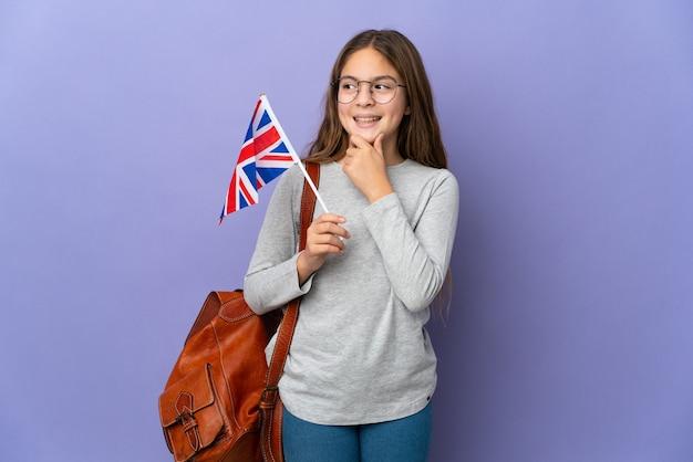 Ребенок держит флаг соединенного королевства на изолированном фоне, глядя в сторону и улыбается