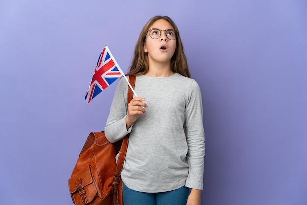 Ребенок держит флаг соединенного королевства на изолированном фоне, глядя вверх и с удивленным выражением лица