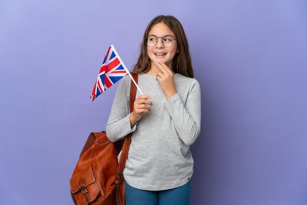 Ребенок держит флаг соединенного королевства на изолированном фоне, глядя вверх, улыбаясь