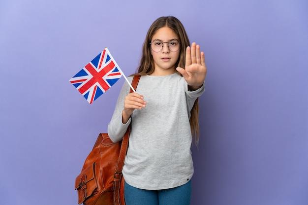 停止ジェスチャーを作る孤立した背景の上にイギリスの旗を保持している子供