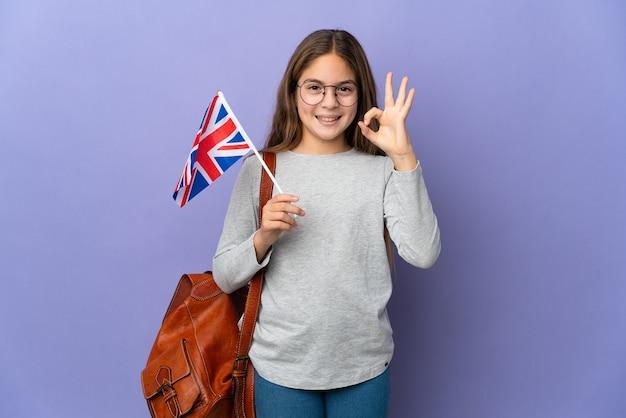 Ребенок держит флаг соединенного королевства на изолированном фоне, показывая пальцами знак ок