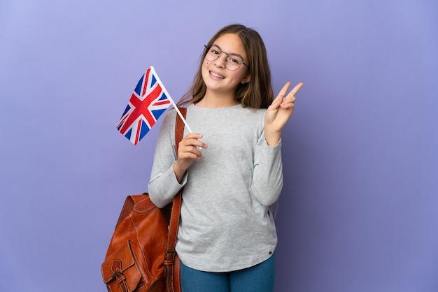 Ребенок держит флаг соединенного королевства на изолированном фоне, улыбаясь и показывая знак победы