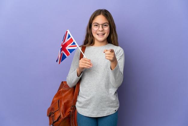 격리 된 배경 위에 영국 국기를 들고 아이 놀라게 하 고 앞을 가리키는