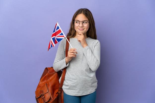 Ребенок держит флаг соединенного королевства над изолированной стеной и смотрит вверх