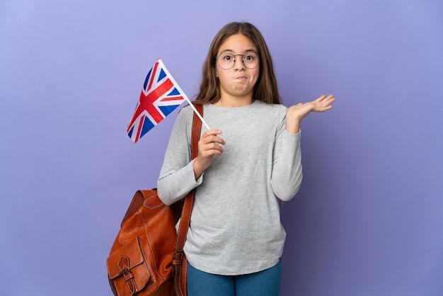 Ребенок держит флаг соединенного королевства над изолированной стеной, сомневаясь, поднимая руки