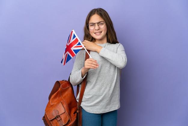 Ребенок держит флаг соединенного королевства над изолированной стеной и страдает от боли в плече из-за того, что приложил усилие