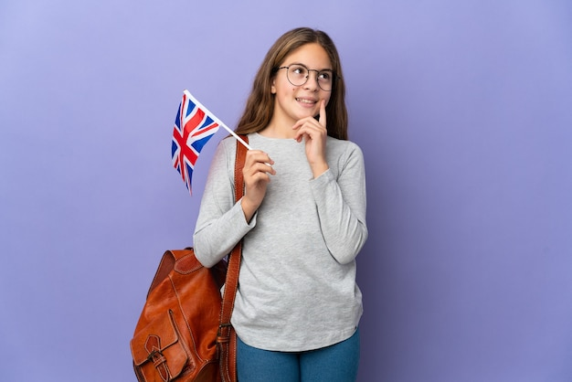 찾고있는 동안 고립 된 벽 생각을 통해 영국 국기를 들고 아이