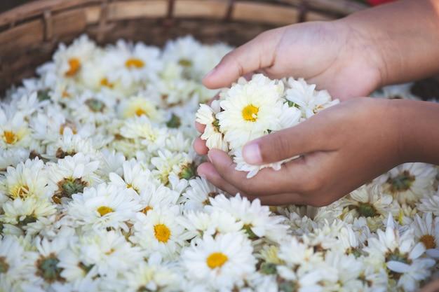 花のバスケットで美しい花を抱く子供