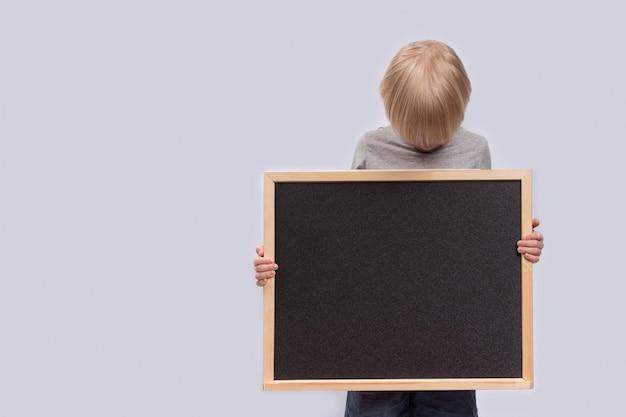 黒板を保持し、それを見ている子。スペースをコピーします。テンプレート。モックアップ