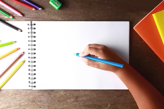 A child holding a blue pencil drawing on a white paper.