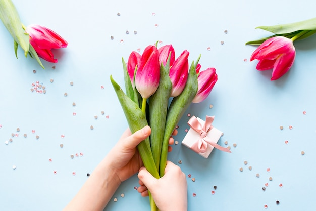 Child holding bouquet of beautiful pink tulips on blue pastel background with sparkling decor and little white gift box.