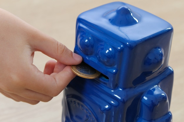Child holding a brazilian real coin and inserting into a cute blue robot coin bank