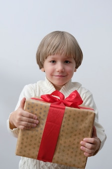 Child holding christmas gift box in hand. boy isolated on white background. new year and x-mas concept.