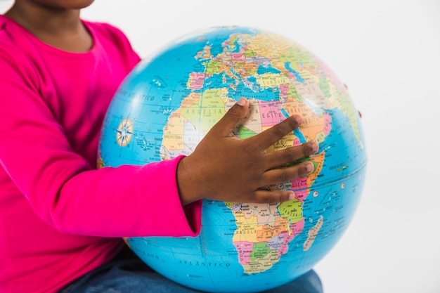 Child holding globe in studio