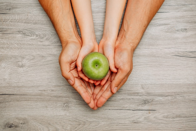 Child holding a green apple in her hands inside of her father's hands top view on a light wooden