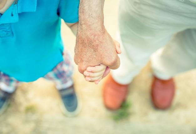 Ребенок, держащий руку старшего человека на фоне пути природы. концепция двух разных поколений.