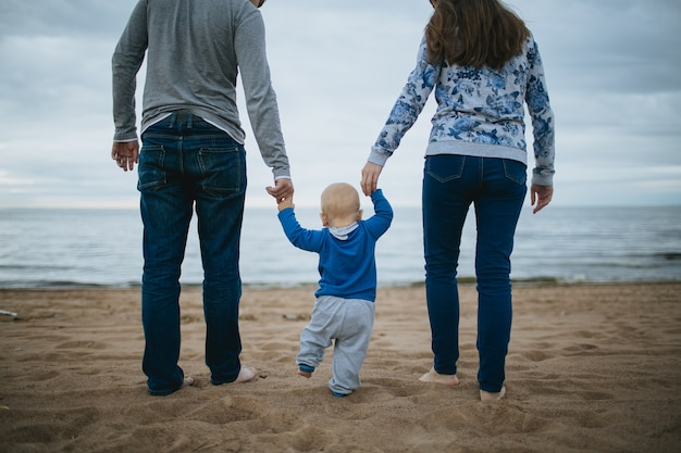 Child holding hands of his parents and walking on the sand.