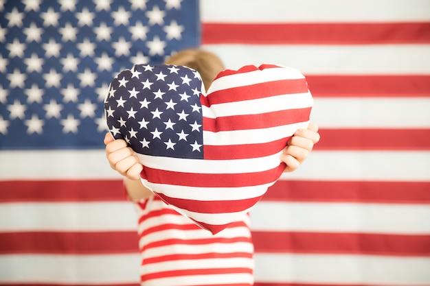 Ребенок держит сердце напечатанный американский флаг 4 июля праздник день независимости