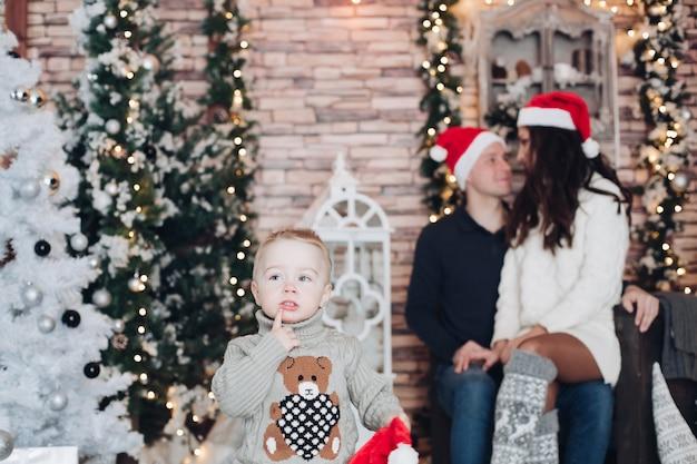 그의 사랑하는 부모가 크리스마스 트리 옆에 앉아있는 동안 아이는 입에 가까이 그의 손가락을 들고