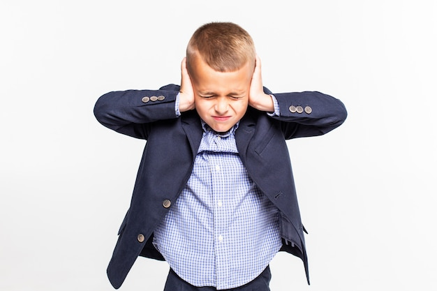 Bambino che tiene le mani contro le orecchie a sopra un muro bianco