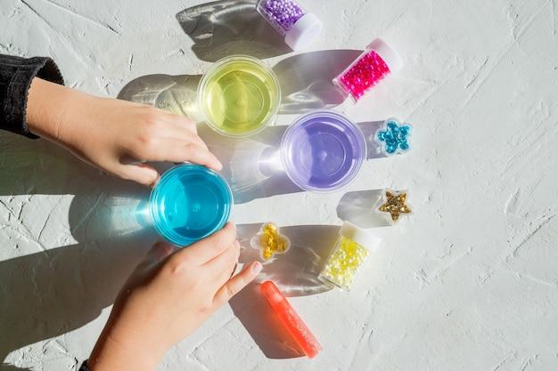 접착제로 인기있는 어린이 장난감을 만들기위한 재료, 병, 항아리를 들고있는 아이.