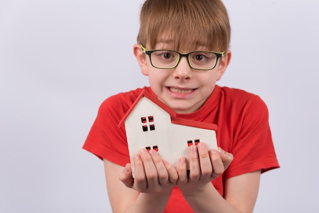 Child holding model of house on white wall