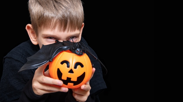 A child holding an orange pumpkin-shaped basket with a grinning face, jack's lantern and a bat on a black background. the boy is waiting for halloween candy. trick or treat tradition.