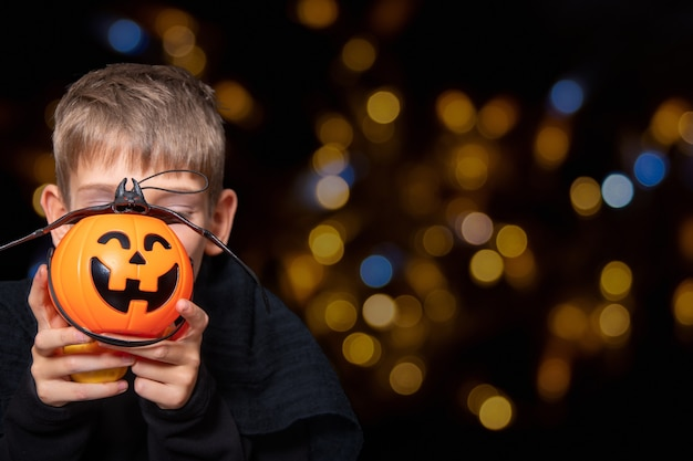 A child holding an orange pumpkin-shaped basket with a grinning face, jack's lantern and a bat on a black background with bokeh. the boy is waiting for halloween candy. trick or treat tradition.