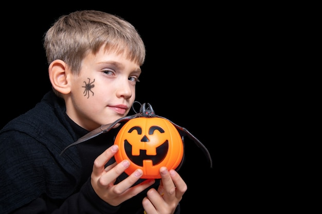 A child holding an orange pumpkin-shaped basket with a grinning face, jack's lantern and a bat. a boy with a spider on his cheek is waiting for halloween candy. happy halloween concept