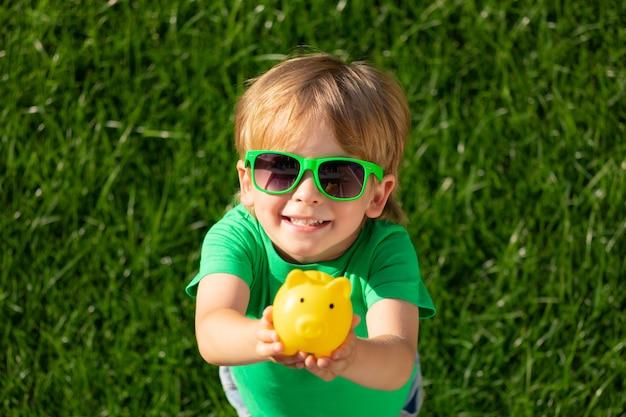녹색 봄 배경 손에 돼지 저금통을 들고 아이. 환경 보호 개념을위한 모금 행사