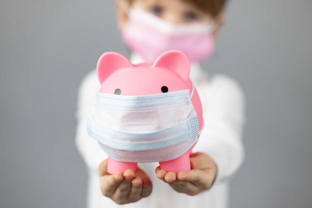 手に保護医療マスクを身に着けている貯金箱を保持している子供。コロナウイルスcovid-19パンデミックコンセプト中のビジネス