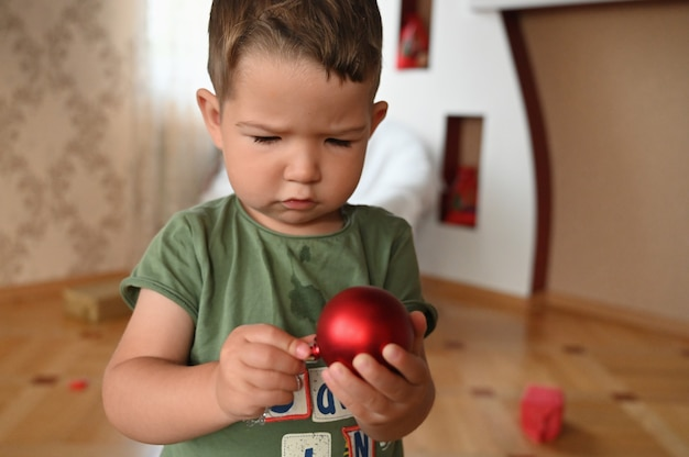 A child holding a red christmas ball. high quality photo