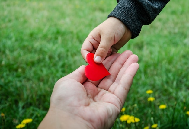 Child holding red heart from his father's hand