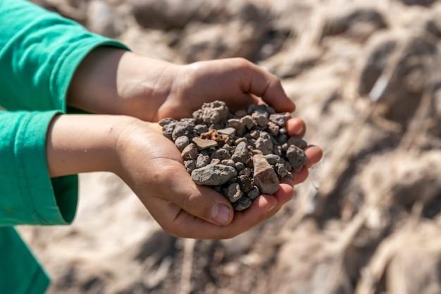小さな手に小さなカラフルな石を持っている子供。ゲームマネーの概念、貴重なリソース