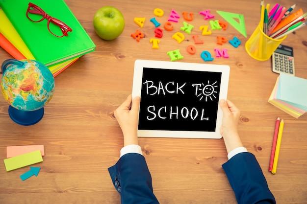 태블릿 pc를 손에 들고 있는 아이. 수업 시간에 나무 책상에 있는 학교 용품. 교육 개념입니다. 평면도