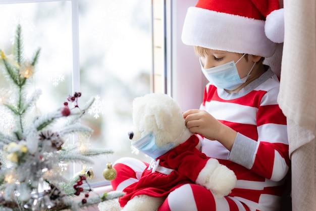 코로나바이러스 개념 동안 크리스마스 의료용 마스크를 쓴 아이의 테디 베어 초상화를 들고 있는 아이