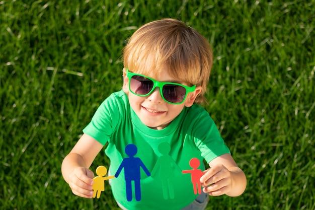 春の緑の背景におもちゃの家族を手に持っている子供。夢と想像力の概念