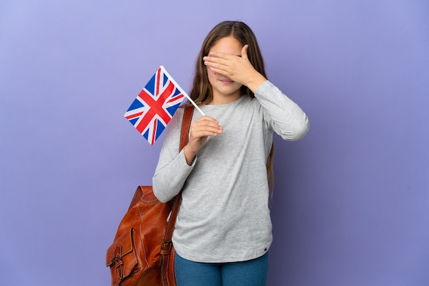 Child holding an united kingdom flag over isolated background covering eyes by hands. do not want to see something