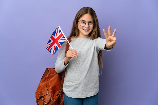 Child holding an united kingdom flag over isolated background happy and counting three with fingers