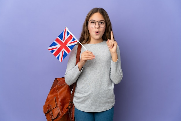 Child holding an united kingdom flag over isolated background intending to realizes the solution while lifting a finger up