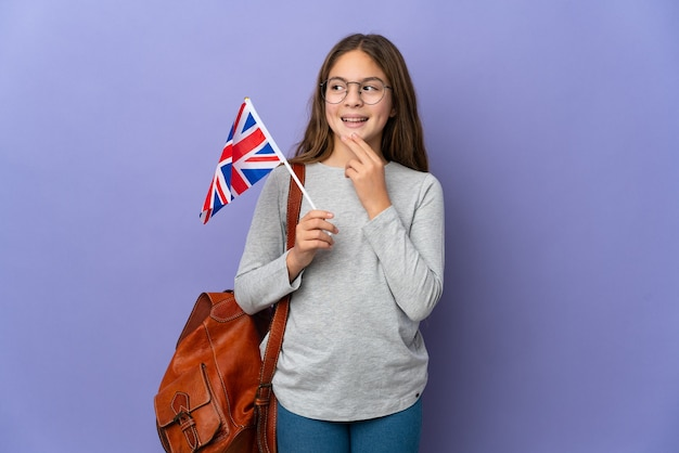 Child holding an united kingdom flag over isolated background looking up while smiling