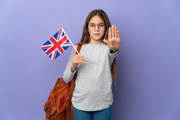 Child holding an united kingdom flag over isolated background making stop gesture