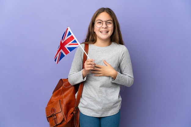 Child holding an united kingdom flag over isolated background smiling a lot