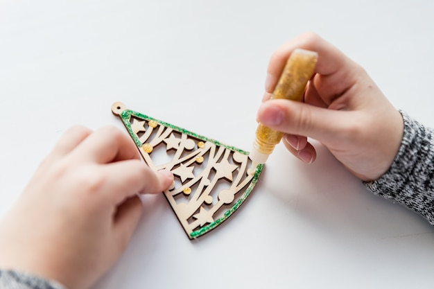Child holding a wooden christmas tree toy. wooden christmas tree decorated with shiny glitter gel. new year crafts idea for kids.creative hobby mockup. diy christmas handmade presents and decoration