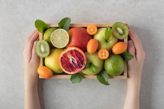 トロピカルフルーツの盛り合わせと木製の箱を保持している子灰色の背景、俯瞰