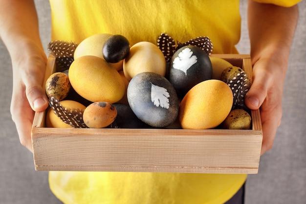 Ребенок держит деревянный ящик с естественно окрашенными пасхальными яйцами на сером фоне.