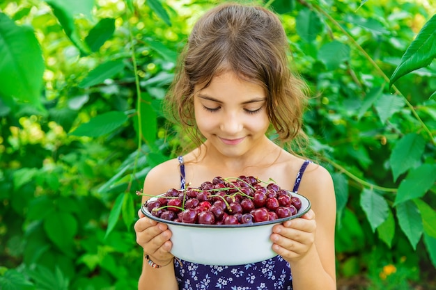 아이는 정원 배경에서 체리와 그릇을 보유