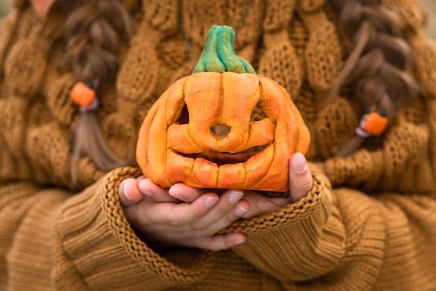Ребенок держит маленькую тыкву на хэллоуин
