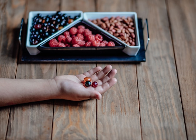 Child holds berries in the palm of his hand over a wooden table vases with raspberries and currants